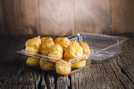 creampuff: Cream Puffs in Plastic packaging on wooden background.