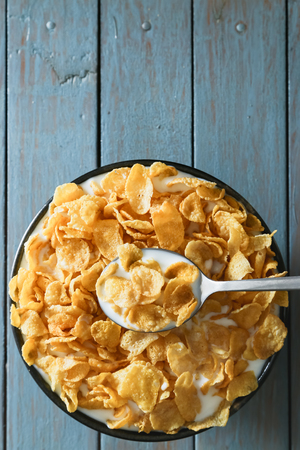 cornflakes with milk on wooden table