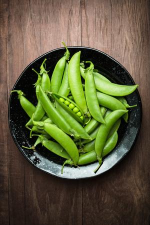raw food: Fresh peas on woodden background Stock Photo