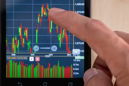 nyse: Trading on stock market with smartphone. Closeup photo.