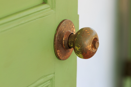 door knobs: Door knobs made of brass with green old wooden door.