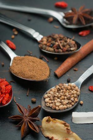 variability: Spices and herbs on black wood background