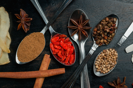 beansprouts: Spices and herbs on black wood background