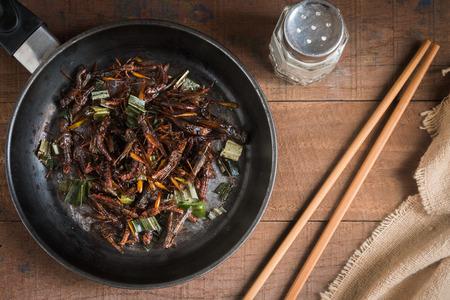 lombriz de tierra: Saltamontes frito con pandan sazone con sal, pimienta y salsa de soja. en la vieja mesa de madera