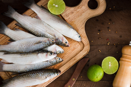 grey mullet: Seafood fresh mullet fish with lime and spice on a old wooden table. top view Stock Photo
