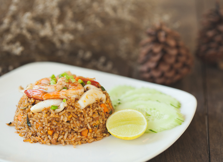 Healthy food spicy fried rice Shrimp with squid on vintage wooden background, selective focus