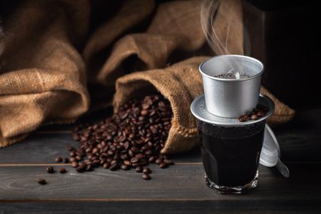 Vintage Vietnam koffiedruppelaar, koffiekopje en koffiebonen met zak. donkere voedselstijl