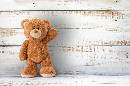 Cute teddy bear with copy space on white color wood background.