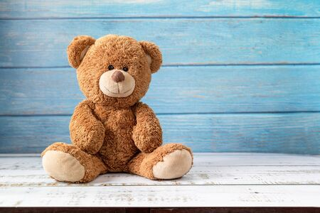 Cute teddy bear with copy space on blue color wood background.