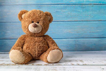 Netter Teddybär mit Kopienraum auf blauem Holzhintergrund. Standard-Bild