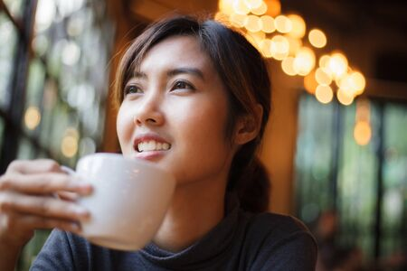 A beautiful woman drinking coffee and relaxing with a smiling face.