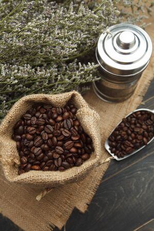 coffee beans, coffee bag and jar on wooden table.