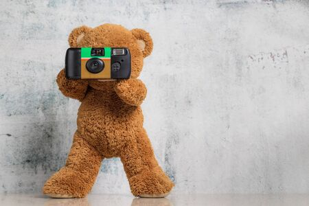 Cute Little teddy bear photographer on white background with copy space