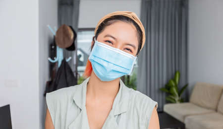 Asian woman smiling behind the mask have a happy face In her house for social distancing concept.