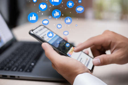 Man person hands holding smartphone for social interaction on social media with notification icons like, heart, comment  message and star, digital marketing and social media concept. Stock Photo