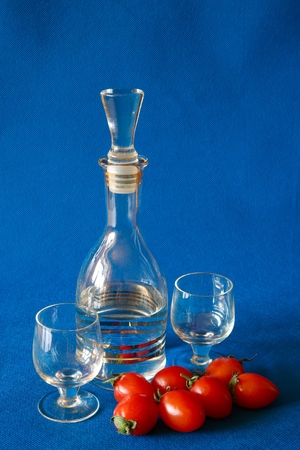 blue background: Decanter and glass, and tomatoes.