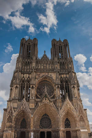 reims: Front aspect of the cathedral in Reims, France shot from below against a blue sky with some white clouds. Stock Photo