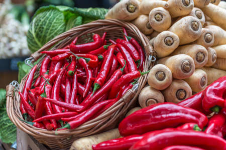 A basket of red chillies displayed on a vegetable stall against a backdrop of parsnips and cabbage photo
