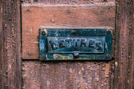 cote d'azur: A weathered metal letterbox in the wooden front door of a French house. Stock Photo