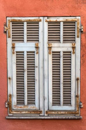 red shutters: White weathered French wooden window shutters on a red wall.