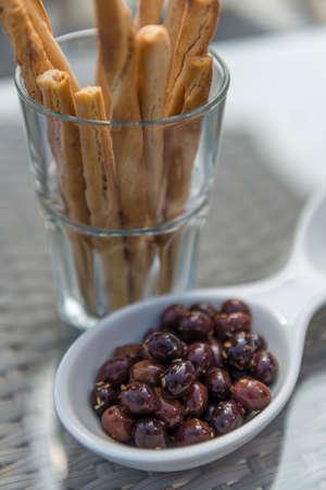 gressins: Petites olives noires dans un bol avec des bâtons dans un gobelet en verre sur une table dans un bar ou un restaurant