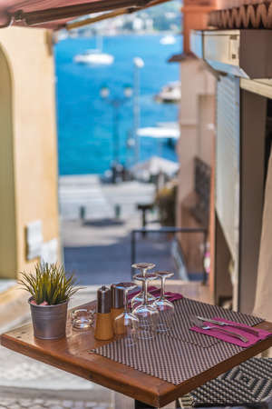 brasserie: A bistro table outside a brasserie with a view of the harbour in the distance Stock Photo