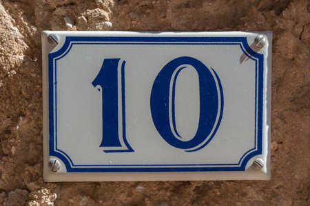 blue plaque: Blue and white number 10 ceramic plaque on a house wall Stock Photo