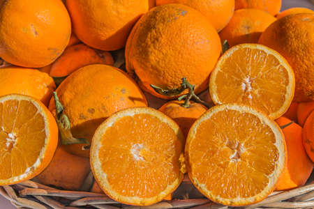 grocers: Fresh local oranges on display with two cut through displaying the juicy cross section