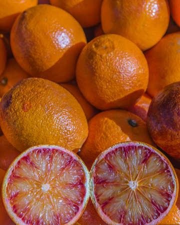 grocers: Fresh local blood oranges on display with one cut through displaying the juicy cross section