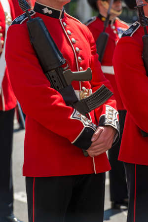 ceremonial clothing: British soldiers wearing red ceremonial uniforms lined up on parade holding a rifle