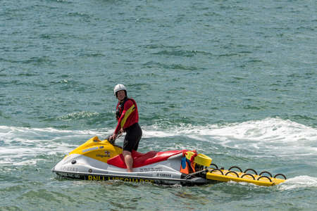 PORTSMOUTH, UK - JULY 25: An RNLI lifeguard on a jetski patrols the beach at the Americas Cup World Series in Portsmouth shown on July 25, 2015 in Portsmouth, UK