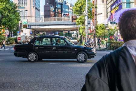 forground: A taxi on a Tokyo street with a potential business passenger in the forground