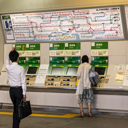 A confused passenger approaching the railway station ticket machines in Tokyo with the system map above