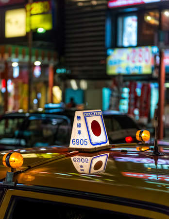 Closeup of a lit taxi sign on the roof of a yellow Japanese taxi on call at night
