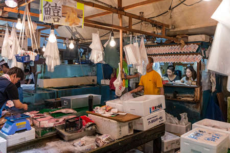 Tsukiji wholesale fish market in action early in the morning with traders in action on a stall Editorial