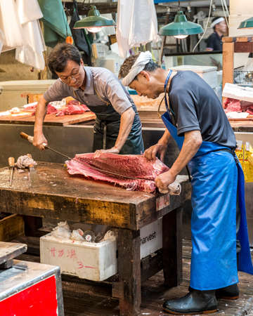 Two traders in Tsukiji wholesale fish market preparing a tuna fish with a large knife on a stall