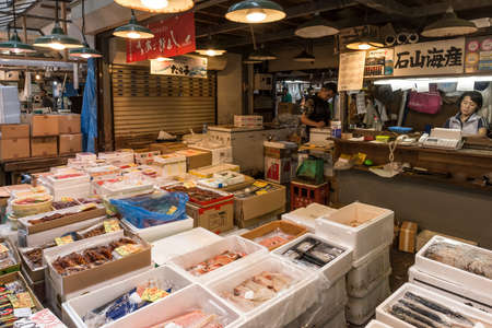 Tsukiji outer wholesale fish market in action early in the morning with traders in action on a stall Editorial