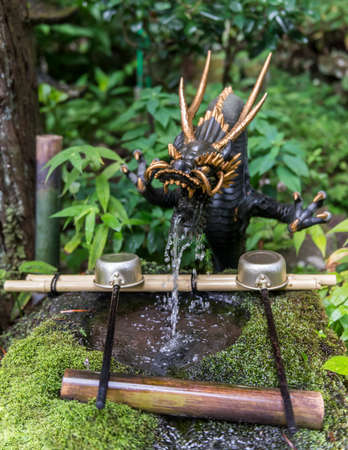 Dragon water fountain at a shrine with laddles for washing as a part of the ritual before entering the shrine