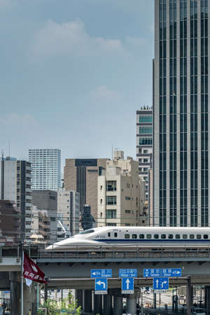 A Tokaido shinkansen bullet train speeds across a bridge over a city street in Tokyo shown on August 7, 2015 in Tokyo, Japan Editorial