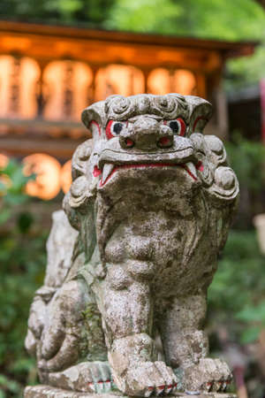 Stone guardian lion dog with Japanese lanterns in the background