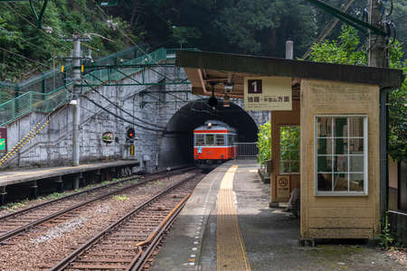 A Hakone Tozan line train comes out of the tunnel mouth at Tonosawa station