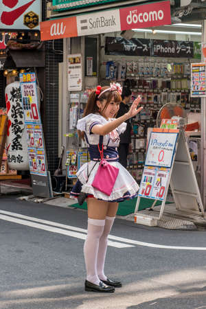 Japanese girl trying to entice people into maid cafe in Akihabara