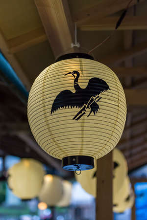 A paper lantern with a cormorant logo on it hanging from the roof of a tourist boat Imagens