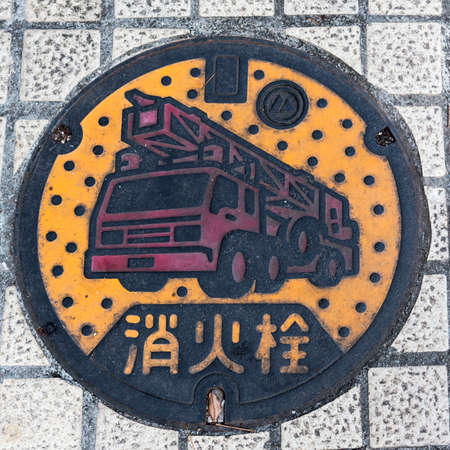 Round manhole cover in a path with the words Fire Hydrant in Japanese on it Imagens