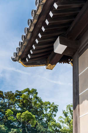 Traditional Japanese ornate wooden roof overhang with gold decoration