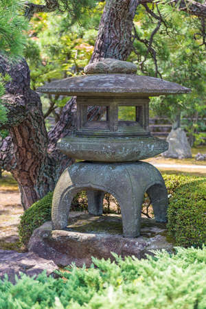 Ornamental stone pagoda sculpture in a traditional formal Japanese landscape garden