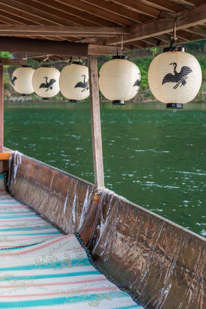 Paper lanterns with a cormorant logo on them hanging from the roof of a tourist boat Imagens