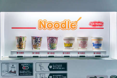 display machine: A line of cup noodles on display for purchase in a vending machine