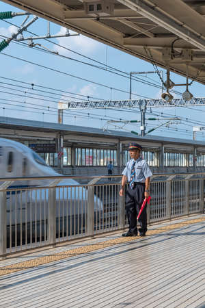 A member of station staff keeping watch on a platform while a Shinkansen bullet train passes Editorial