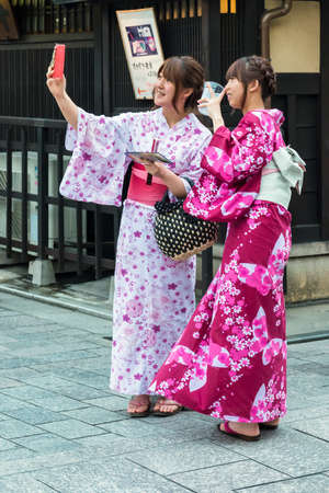 Two Japanese girls dressed in kimonos taking a selfie